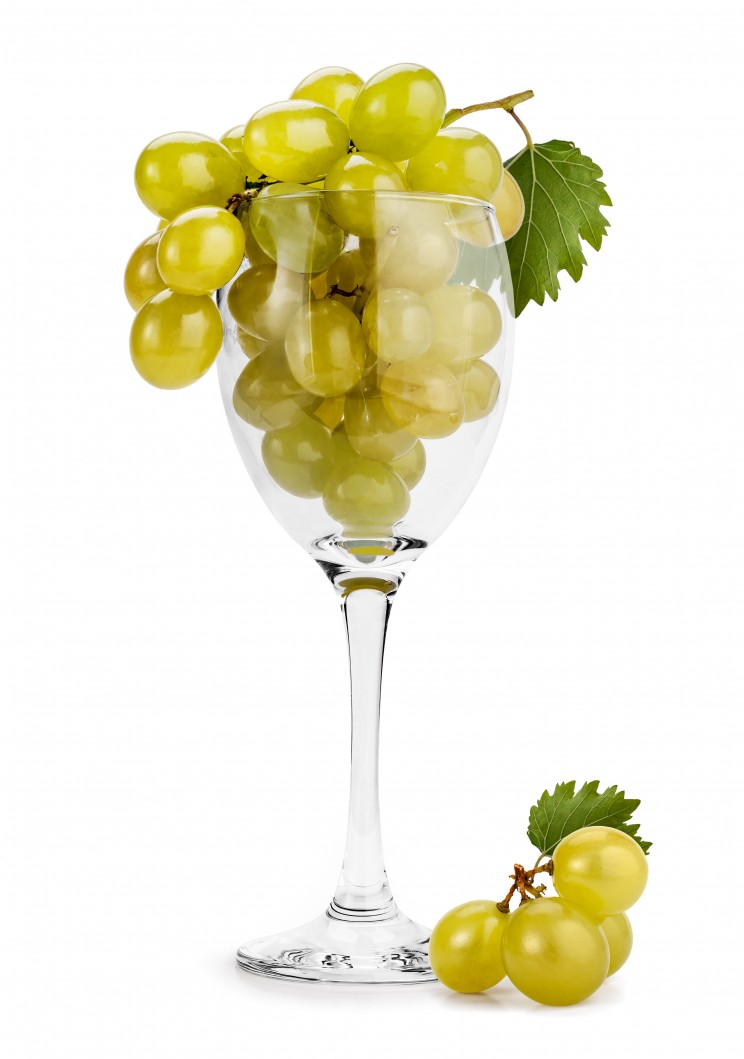 Green grape (Muscat) cluster in a wine glass isolated on white.