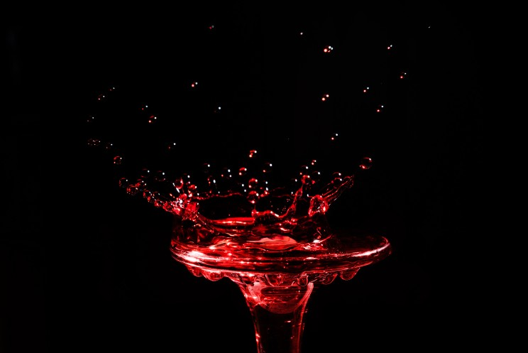 Close-up a drop of wine in the form of a crown is split on the glass  isolated on a black background.